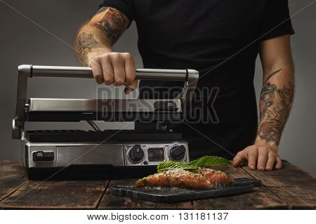 Man Cooks Healthy Meal, Prepares Electronic Home Grill To Roast Two Raw Pieces Of Salmon Decorated W