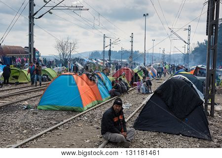 IDOMENI, GREECE - MARCH 17, 2015: Refugees from Syria sit by their tents on March 17, 2015 in the refugee camp of Idomeni, Greece. For several weeks more than 10.000 refugees and immigrants wait here for the borders to open.