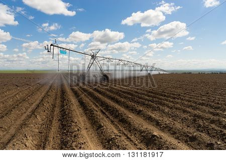 A watering sytem moves along on top of the freshly plowed field