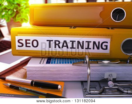 SEO - Search Engine Optimization - Training - Yellow Office Folder on Blurred Background of Working Table with Stationery and Laptop. Business Concept. SEO Training Toned Image. 3D.