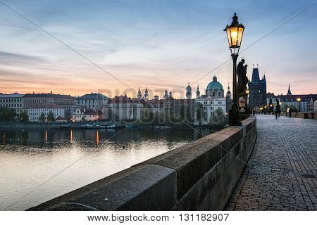 Charles Bridge at sunrise, Prague, Czech Republic. Dramatic statues and medieval towers. Unique view at dawn when there are almost no people on the bridge.
