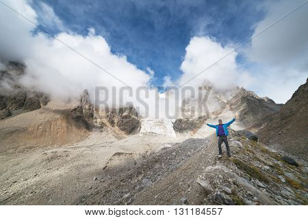 Mountain landscape. Tourist standing on the crest of the ridge. Mountain glacier. Beauty in nature. Hiking on the mountain peaks. Caucasus, Georgia, Zemo Svaneti
