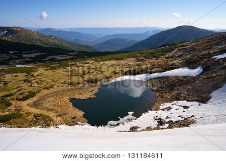 Spring in the mountains. Landscape with a lake. Last snow on the slopes. Sunny day with blue sky. Carpathians, Ukraine, Europe. Beauty in nature