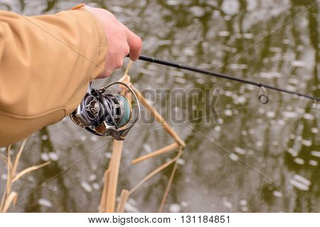 Fishing in river.A fisherman with a fishing rod on the river bank. Man fisherman catches a fish.Fishing spinning reel fish Breg rivers. - The concept of a rural getaway. Article about fishing.