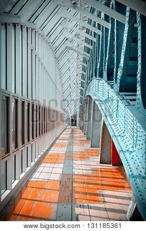 Indoor pedestrian bridge. Glass windows stretching into the distance. Perspective. A lot of repetitive elements. Pedestrian zone.Vintage tinted.
