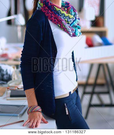 Beautiful fashion designer standing in studio