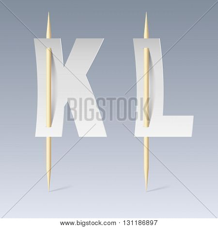 White paper cut font on toothpicks on grey background. K and L letters