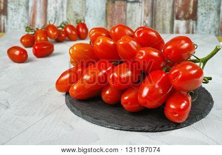 Fresh ripe mini roma tomatoes on grey board and multicolored background