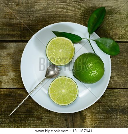 Lime in the white plate with old spoon on wooden background