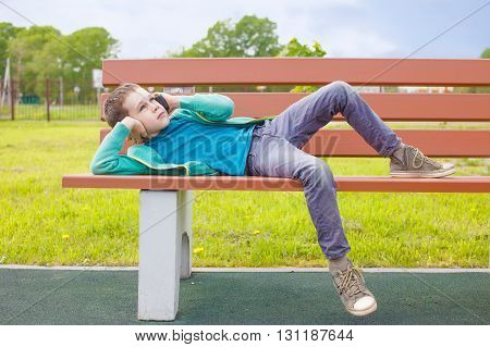 child talking on the phone while lying on a bench. bored boy waiting for the call is finished