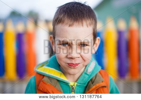 sad kid holds back tears. boy on the playground trying not to cry from the pain or resentment