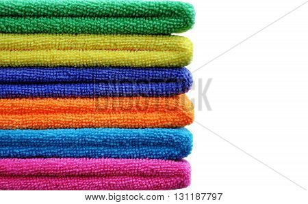 A stack of neatly folded coloured towels on white background