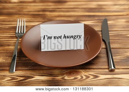 Brown plate on a brown wooden table, i am not hungry