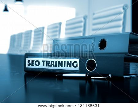 Office Binder with Inscription SEO Training on Wooden Desktop. SEO Training - Office Folder on Wooden Desk. 3D Render.