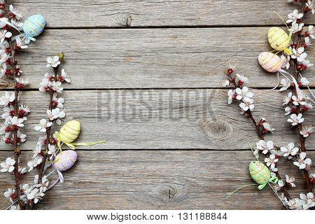 Tree branches with flowers and easter eggs on grey wooden table