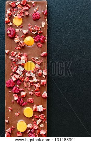 Top view of an orange strawberry and raspberry milk chocolate tablet on a black grainy background.