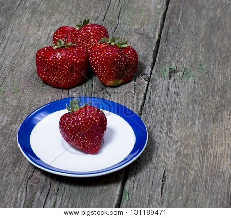strawberry on a saucer and behind three strawberries a berry subject spring