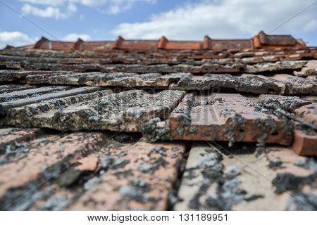 Aged Roofing Tiles On Old House In Village On Blue Cloudy Sky