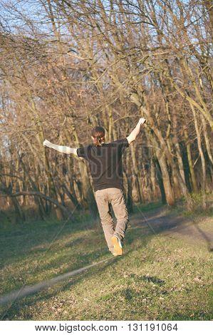 Man walking on slackline in the park