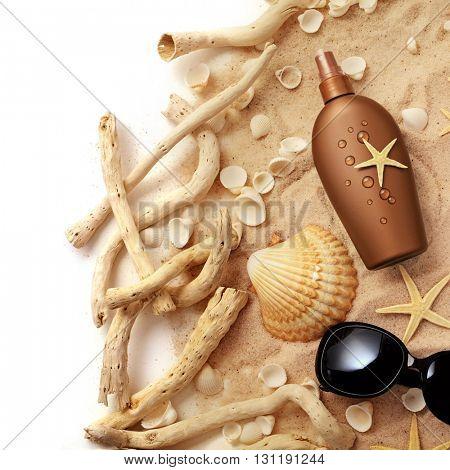 suntan cream bottle and sunglasses on sand beach