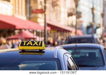 the yellow symbol or sign with an inscription of a taxi is located on a car roof on an indistinct background city and blank space
