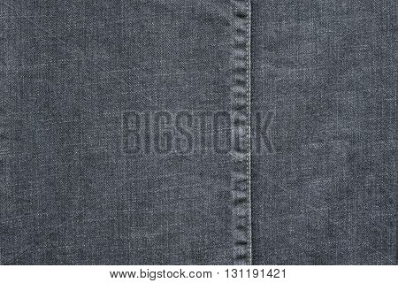 denim or rough cotton fabric or jeans material with the stitched seam for the textile textured background of pale color