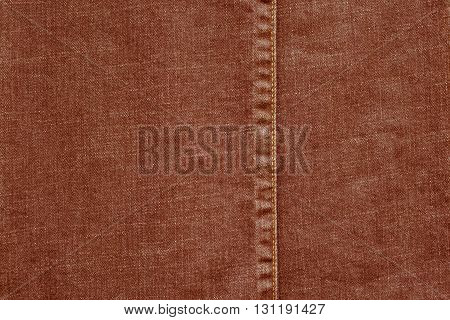 denim or rough cotton fabric or jeans material with the stitched seam for the textile textured background of pale red color