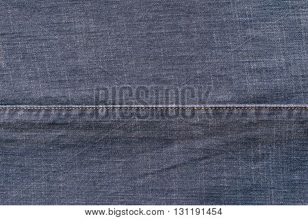 denim or rough cotton fabric or jeans material with the stitched seam for the textile textured background of pale blue color