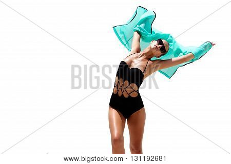 Dancing woman in black swimsuit sunglasses and turquoise beach dress poses on white isolated background. High fashion look.  Hair up
