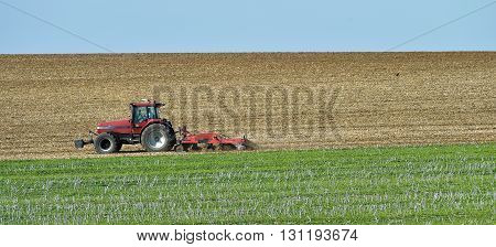 View of tractor ploughing through field, Champagne-Ardennes, France, Europe