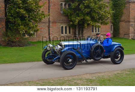 Saffron Walden, Essex, England - April 24, 2016: Vintage blue racing car being driven past  front of old building.