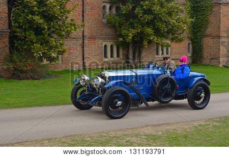 Saffron Walden, Essex, England - April 24, 2016: Vintage blue racing car being driven past  front of old building.