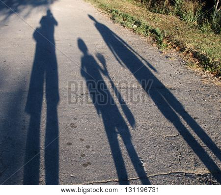 Shadows of men, woman and child on the pavement