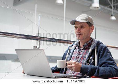 Man with laptop drinking coffee in a cafe
