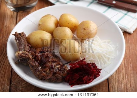 Beef cutlet with boiled potato, beetroot, and daikon radish