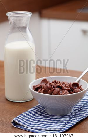 Breakfast flakes with milk on a kitchen table