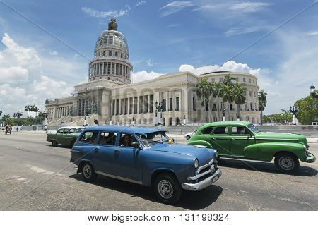 Havana, Cuba - June 22, 2015: Classic american cars passing by the Capitolio in Old Havana
