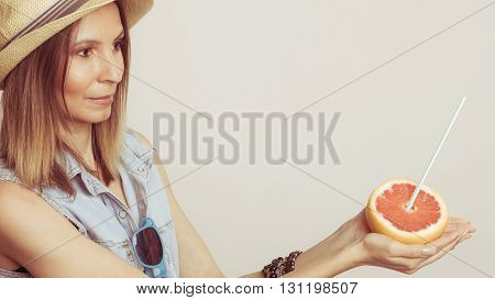 Happy glad woman tourist in straw hat with sunglasses and grapefruit citrus fruit. Healthy diet food. Summer vacation holidays concept.