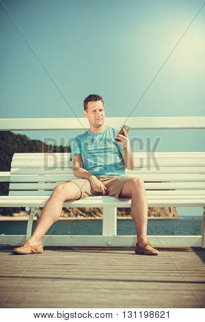 Handsome man tourist sitting on bench on pier using smartphone. Fashion guy enjoying summer travel vacation by sea. Relax and technology concept.
