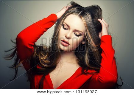Beautiful young and emotional caucasian woman model with sensitive lips posing at studio in the light flashes. Great long natural hair.