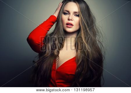 Beautiful young and sexy caucasian woman model with deep blue eyes and sensitive lips posing at studio in the light flashes. Great long natural hair.