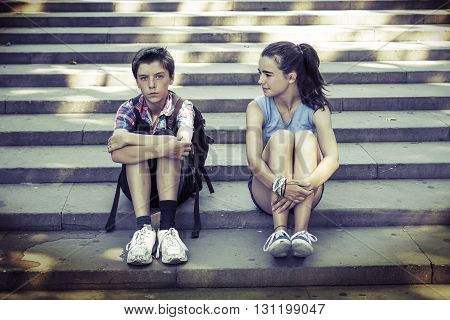 tired travelling siblings sitting on steps in summer