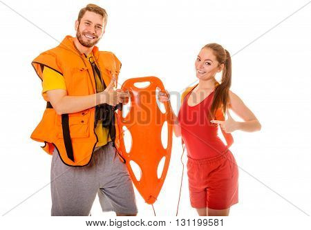 Lifeguards in life vest jacket pointing at rescue tube buoy. Man and woman supervising swimming pool. Accident prevention.