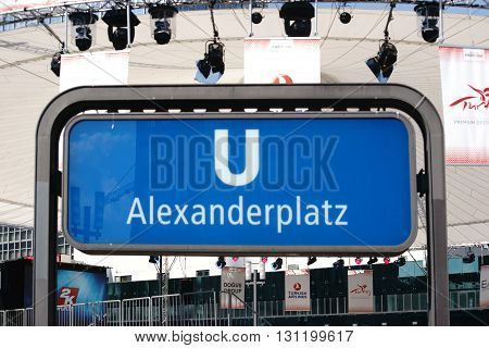 BERLIN, GERMANY - MAY 10: The blue sign of the underground station Berlin Alexander Place with a constructed stage tent in the background on May 10, 2015 in Berlin.