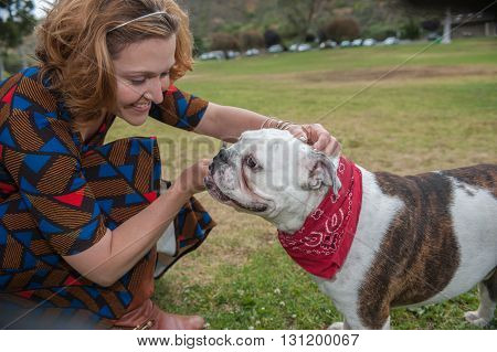 Attractive woman and her English Bulldog puppy with faces close.