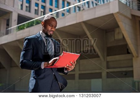 Black Businessman Looking At His Tablet Computer In Urban Background03