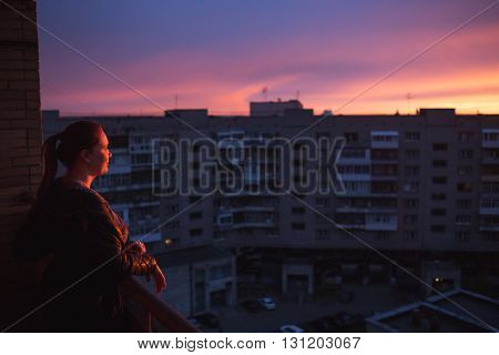 Silhouette of woman enjoying the city view on sunset. Concept of loneliness, eternity, choice