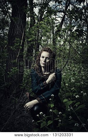 Redhead scandinavian woman posing with sword in a forest