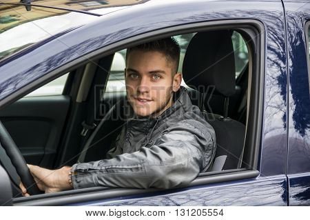 Handsome young man at wheel of his car while looking at camera