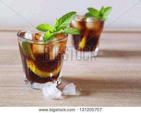 Cocktail Long Island with mint garnish, two glass